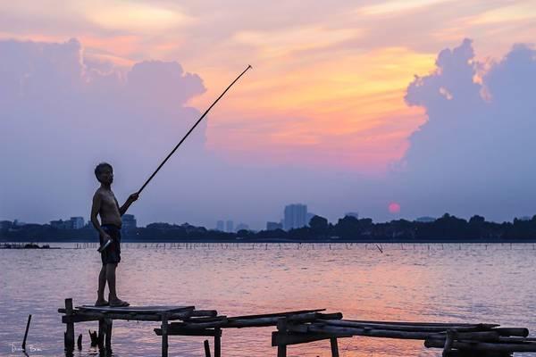 Một người đàn ông đang buông cần trên Hồ Tây.