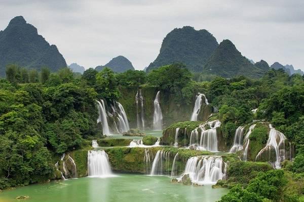 Description: 2. Thác Bản Giốc: Thác Bản Giốc được đánh giá là thác lớn thứ 4 trên thế giới. Thác nước này thuộc xã Ðàm Thủy, huyện Trùng Khánh, tỉnh Cao Bằng gồm hai phần: phần phía nam gọi là thác cao, lượng nước không nhiều, thác Thấp nằm ở biên giới giữa hai nước Việt và Trung nằm ở phía Bắc. Phần thác Thấp rộng khoảng 100 m, cao 70 m và sâu 60 m, giữa thác có mô đất phủ đầy cây, cắt xẻ dòng thác thành ba luồng chính. Nhìn từ xa thác như một tấm lụa trắng xóa đươc bao phủ bởi thảm thực vật bìa rừng vô cùng tuyệt đẹp như chốn tiên cảnh. Ảnh: Dulichtaynguyen.