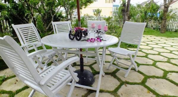 Bộ bàn ghế xinh xắn đặt trong sân khách sạn, nơi để du khách nghỉ chân ngắm cảnh.