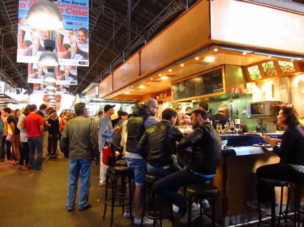 Du khách bên quầy hàng ăn ở chợ Boqueria - Ảnh: wp