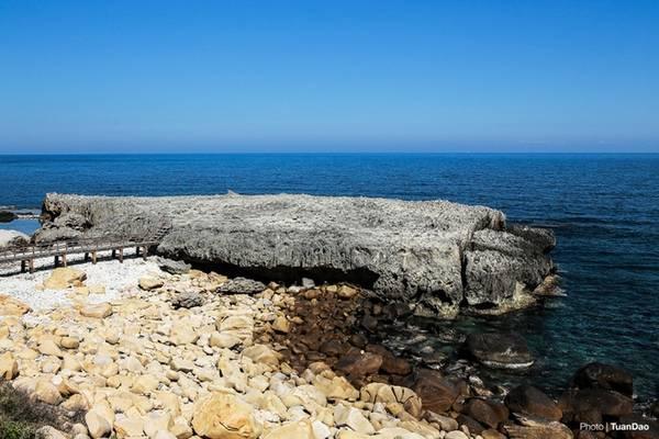 Nhìn từ xa, vách đá xù xì, hiểm trở trông như một phi thuyền khổng lồ, nổi bật trong nền nước biển xanh thẳm.