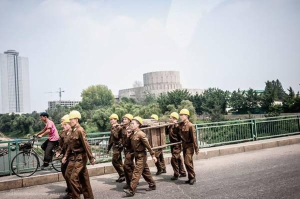 """Các công nhân xây dựng đang """"hành quân"""" qua một cây cầu."""