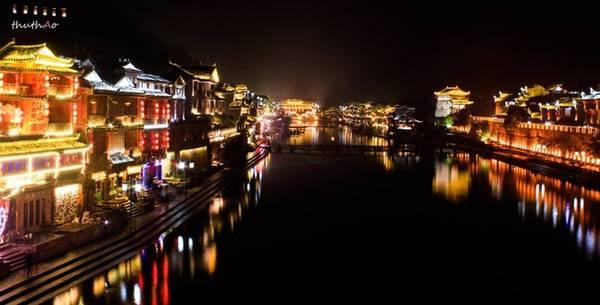 Khi màn đêm buông xuống, Phượng Hoàng cổ trấn trở nên lung linh huyền ảo như tìm về hào quang của 1.300 năm trước. Cả một khúc sông Đà Giang rực rỡ trong ánh đèn lồng, những ngôi nhà bên sông thêm sắc màu, tô điểm cho không gian cổ kính nên thơ.