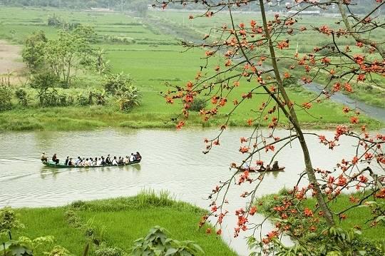 Ngồi trên chiếc thuyền nhỏ, ngắm nhìn sông nước và những chùm hoa đỏ rực rỡ tại chùa Hương.(Ảnh: Internet)
