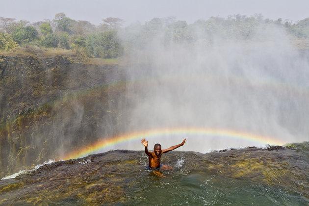 Khi tung tăng bơi lội trong bể bơi, bạn sẽ được tận mắt chiêm ngưỡng quang cảnh thiên nhiên hùng vĩ ngay trước mắt. Đặc biệt, hơi nước kết hợp với ánh mặt trời châu Phi sẽ tạo nên những cầu vồng khổng lồ tuyệt đẹp, lửng lơ bắc ngang qua vực thẳm.Ảnh: Yvette Cardozo/Getty Images