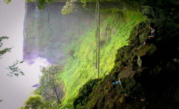 Bạn trẻ ngồi bên hông thác, ngắm nước chảy - Ảnh: Trí Tài