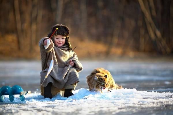 Một em bé ở Nga đang câu cá dưới dòng sông băng.
