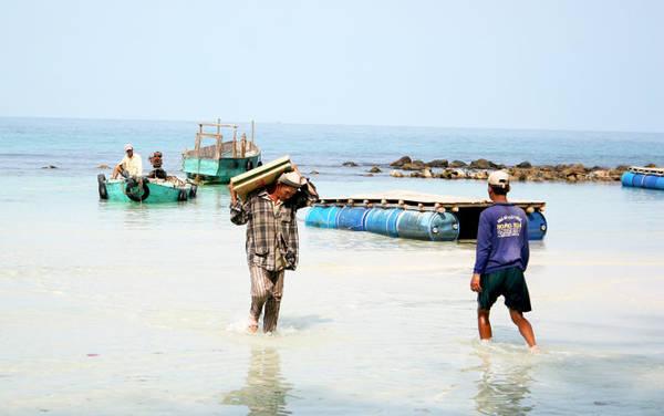 Chiếc ghe nhỏ chở đồ đạc từ đảo lớn về hòn Mấu - Ảnh: Minh Đức