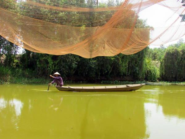 Một cụ bà bơi xuồng trên dòng kênh trong khu bảo tồn sinh thái Thạnh Tân - Ảnh: N.T.Đăng