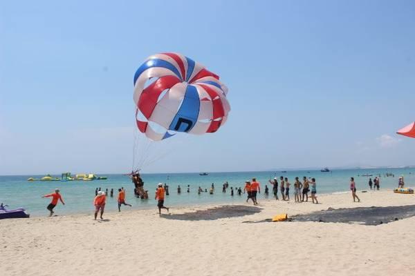 Ngắm toàn cảnh bãi biển xinh đẹp từ tên cao với trò chơi dù lượn.