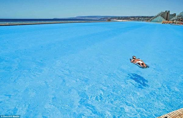 Du khách thảnh thơi tắm nắng giữa bể bơi mênh mông, không phải chịu cảnh chen chúc giữa trời nóng bức. Ảnh: Barcroft Media.
