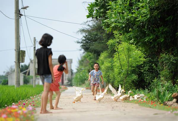 Sự chăm chút của người lớn đã giúp cho các em nhỏ có thể vui chơi trên những con đường sạch sẽ, lãng mạn sắc hoa.