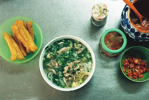 Bát phở nóng hổi được người nấu bưng ra thơm ngậy, rắc thêm chút tiêu, thêm vài lát ớt tươi, tương ớt, vắt chanh và ăn cùng vài chiếc quẩy. Ảnh: Phong Vinh