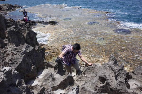 Để xuống được tầng dưới của quần thể đá, du khách phải cẩn trọng trèo qua các mỏm đá nhọn - Ảnh: HUYỀN TRANG