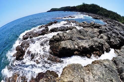 Bãi đá trầm tích quanh miệng núi lửa cổ bị tách thành nhiều cụm nên nước biển xô bờ tung trắng xóa chảy thành vệt dài theo kẽ đá như những dòng suối. Ảnh: Trí Tín