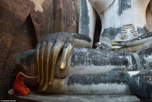 Một nhà sư chạm tay vào bức tượng Phật khổng lồ tại chùa Wat Si Chum ở Thái Lan.