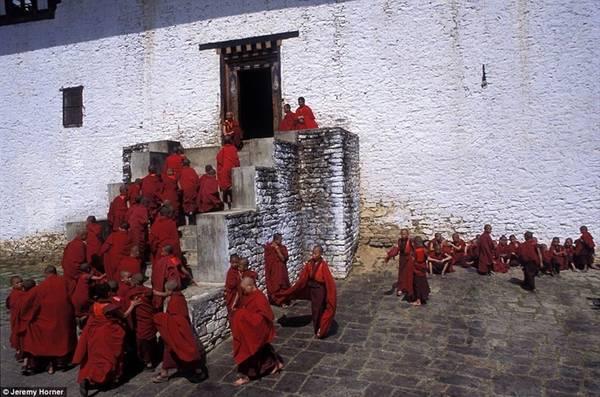 Mặc áo choàng màu đỏ rực rỡ, các nhà sư mới chuẩn bị bước vào lễ cầu nguyện sau khi nghỉ ngơi trong sân của tu viện Semtokha ở Thimphu, Bhutan.
