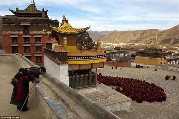 Một khách hành hương dừng lại cầu nguyện trước một đám đông các nhà sư đang tụ tập bên ngoài sảnh cầu nguyện chính của Tu viện Labrang ở Trung Quốc. Được thành lập vào năm 1709, Labrang từng là nơi tu hành của 4.000 nhà sư, nhưng bây giờ chỉ có khoảng 1.500.