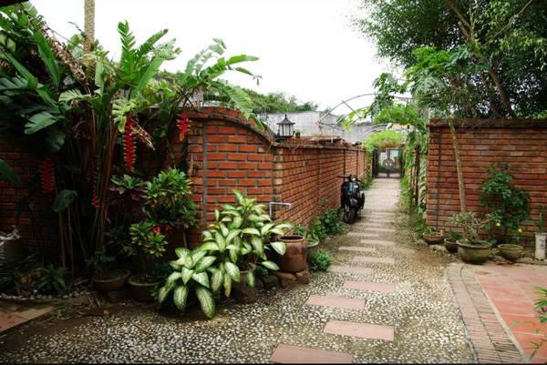 Lối vào nhà bằng tường gạch đỏ.