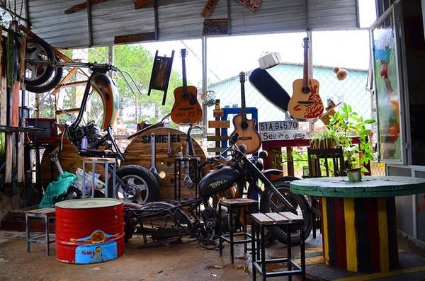 Một góc bên ngoài của quán được lấp đầy bởi chiếc mô tô lắp dở cùng những chiếc đàn ghi ta. Đây là những đồ vật vốn quen thuộc đối với các phượt thủ.