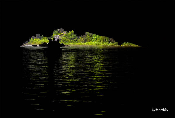 Đi thuyền luồn qua hang. Ảnh: Luis Colás