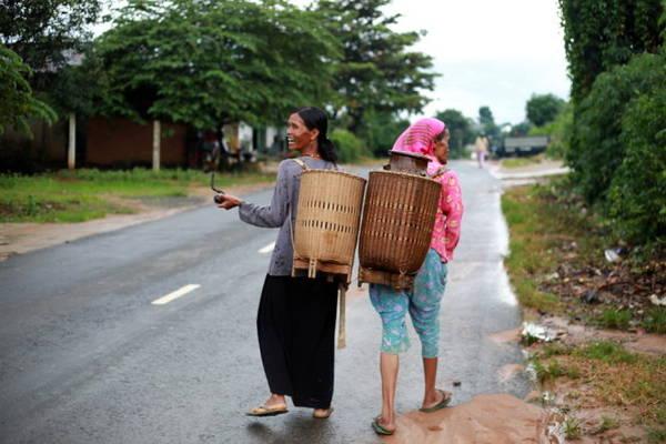 Hai người đàn bà Êđê cầm tẩu thuốc, gùi rau trên quốc lộ 27 đi Đà Lạt sau chiều mưa - Ảnh: TIẾN THÀNH