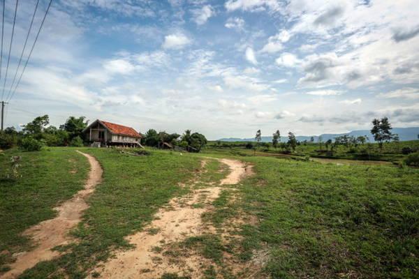 Một nếp nhà dài của người Êđê nổi bật trên bãi cỏ xanh rì ven quốc lộ 26 đoạn qua huyện M'đrắk - Ảnh: TIẾN THÀNH