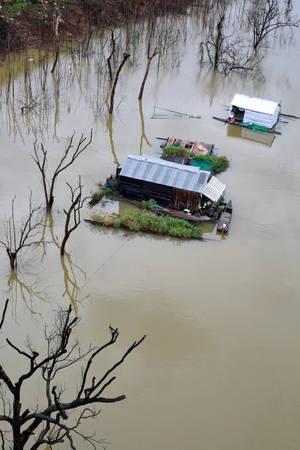 Những ngôi nhà nổi trên một con suối đầy nước thuộc xã Nam Ka, huyện Lắk trong rang chiều - Ảnh: TIẾN THÀNH