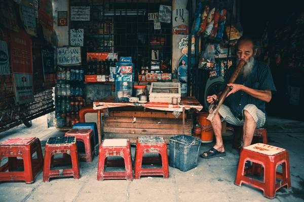 """Cụ Huấn (82 tuổi, ở khu Quỳnh Mai, quận Hai Bà Trưng) tâm sự: """"Tôi đã bán hàng gần chục năm nay. Thuốc lào, trà đá là sở thích từ thuở thanh niên ở làng quê. Bây giờ ở phố, tôi bán hàng vừa kiếm được chút tiền, vừa đỡ nhớ quê""""."""