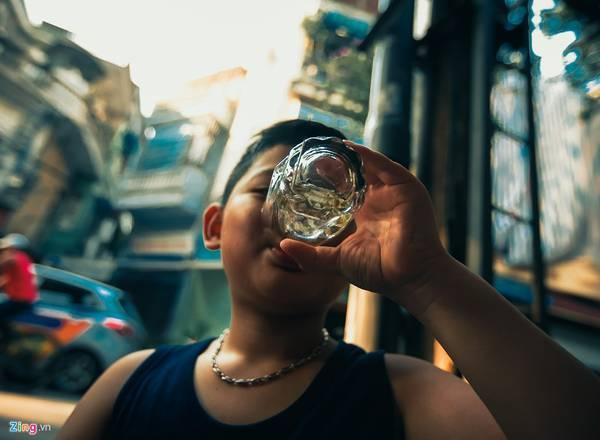"""Một em bé uống trà xanh ở quán nước trên phố Hàng Tre. Trà đá phục vụ cho mọi đối tượng, từ sinh viên, anh xe ôm, đến cán bộ nhà nước... Trà đá chẳng phân biệt giai cấp hay tính cách con người... thậm chí một số nhà nghiên cứu văn hoá của Hà Nội còn đặt cho nó là """" Văn hoá trà đá - Văn hoá vỉa hè""""."""