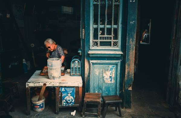 """Cụ bà bán trà đá ở Ô Quan Chưởng. Bà cho biết năm nay đã hơn 80 tuổi, bán nước cũng đã chục năm rồi. """"Nhà chẳng thiếu gì, nhưng cứ thích ngồi bán cho vui, nghe chuyện của thiên hạ"""", bà tâm sự."""