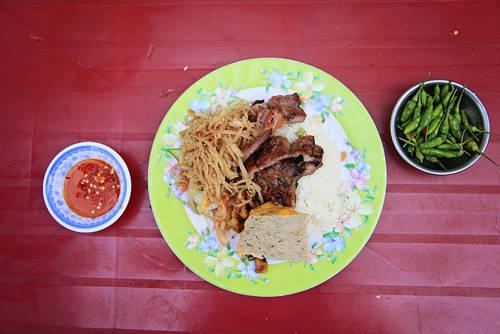 """Cơm tấm sườn bì chả Ngày xưa, cơm tấm là món ăn sáng được chuộng nhất của người dân mọi tầng lớp ở Sài Gòn. Thời nay, món ăn có thể dùng mọi lúc trong ngày từ sáng sớm đến tối mịt. Tuy nó có thể xuất hiện trong những nhà hàng máy lạnh nhưng đối với nhiều người, để thưởng thức món ăn này một cách """"đúng điệu Sài Gòn"""" phải ở một góc đường hay một con hẻm nào đó, với mùi sườn nướng tỏa trong làn khói mờ ảo. Miếng thịt nướng dậy mùi thơm phức ăn chung với miếng chả mềm, sợi bì dai dai, quyện cùng vị mắm mặn vừa phải. Những ai từng ăn qua món ăn này khó lòng mà quên được. Ảnh: Phong Vinh"""
