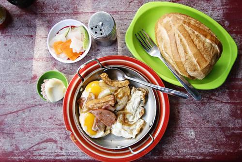 Bánh mì Hòa Mã: Đối với nhiều người, bánh mì là thức ăn nhanh, rất thích hợp đối với cuộc sống tấp nập ở mảnh đất Sài Gòn. Với hương vị khác lạ nhưng không quá đặc biệt, tiệm bánh mì Hòa Mã đã lưu giữ trong mình những kỷ niệm về Sài Gòn từ rất nhiều năm qua. Phần ăn nhiều người hay lựa chọn gồm ổ bánh mì dài khoảng một gang tay, ăn cùng chảo thức ăn nóng hổi, đầy ắp. Bên trong chiếc chảo nhỏ này là đủ thứ nguyên liệu hấp dẫn như trứng gà ốp la, thịt nguội, xúc xích, chả cá, chả lụa,... Tất cả đều được chiên nóng cháy cạnh tỉ mỉ cùng với ít hành tây thái múi cau và dùng nóng với bánh mì. Ảnh: Phong Vinh