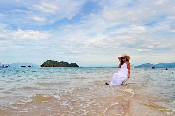 Cô gái đến từ Hà Nội rất thích thú khi ngồi trên chiếc ghế chụp ảnh, trên con đường lúp xúp nước trong lúc thủy triều đang từ từ rút giữa trời biển bao la.