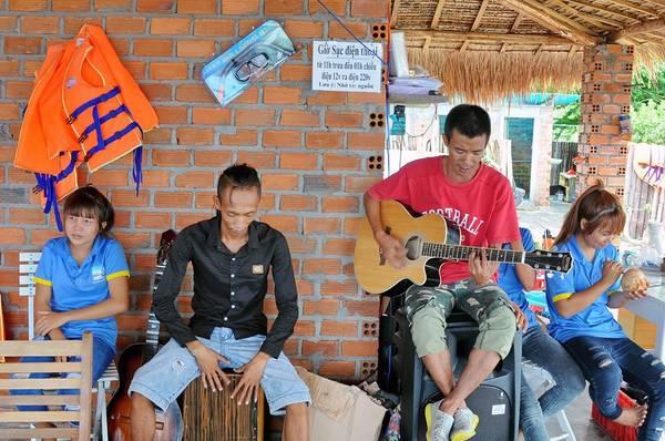 Anh Dương Nguyễn Thanh, nhân viên một công ty lữ hành đàn hát giúp vui cho du khách trong khi chờ thủy triều xuống.