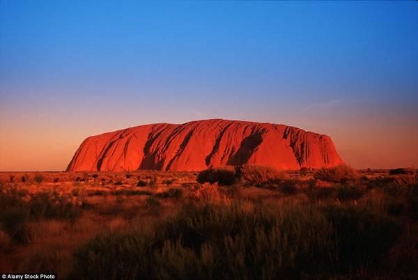 Núi Ayers đỏ rực trong ánh hoàng hôn, nổi bật trên nền trời vùng Outback của Australia.