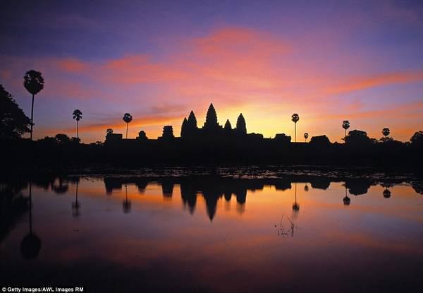 Khu đền Angkor nổi tiếng của Campuchia soi bóng xuống hồ nước trong ánh hoàng hôn tuyệt đẹp, tạo khung cảnh kỳ bí như trong truyền thuyết.