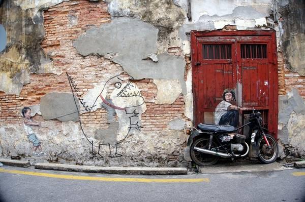 """Bạn thỏa sức tạo dáng """"độc và lạ"""", ghi những bức ảnh lưu niệm bên những tranh tường nổi tiếng, chẳng hạn như bức """"Chú bé trên chiếc xe máy"""", và phía sau là bức """"Đứa trẻ và con khủng long""""."""