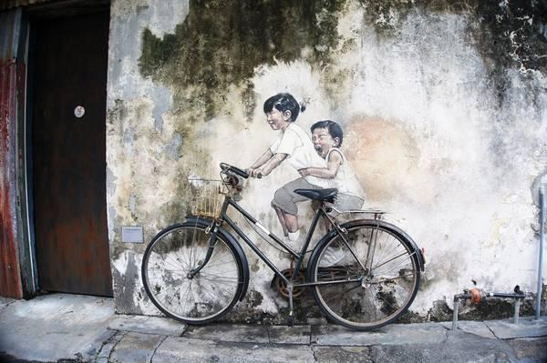 """Bức tranh nổi tiếng """"Những đứa trẻ trên chiếc xe đạp"""" trên góc phố Armenian. Bạn có thể ngồi lên yên xe."""