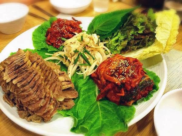 Bossam gồm thịt ba chỉ lợn luộc, cuốn trong lá tía tô cùng cải thảo và ăn kèm kimchi.