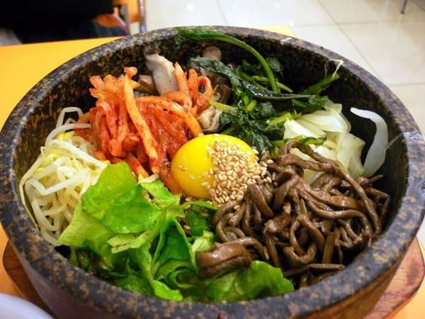 Bibimbap gồm cơm, các loại rau củ, thịt, trứng với tương ớt và dầu mè, được trộn đều và dọn ra trên bát đá nung nóng.