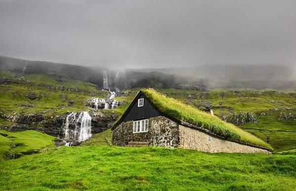 Ngôi nhà làm bằng đá và lợp mái cỏ nằm bên cạnh một thác nước thuộc hòn đảo đẹp như tranh vẽ của Streymoy, Saksun, quần đảo Faroe.