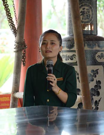 Chị Quỳnh Nga thuyết minh tại khu mộ tập thể của 13 chiến sỹ. Ảnh: Vy An