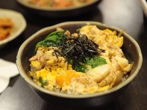 """Oyakodon có nghĩa là """"bát cơm bố mẹ và con"""". Thịt gà, hành và trứng sống được quậy lòng đỏ và trắng cùng với xì dầu, tạo nên món giống ốp lết nhưng được bọc bởi một lớp cơm. Thực chất oyakodon là món cơm gà được nhiều trẻ em yêu thích ở Nhật Bản."""