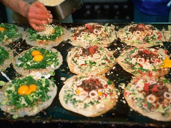 Okonomiyaki là món bánh xèo mặn, đặc sản của vùng Osaka và Hiroshima. Bên trên bánh được cho thêm nhiều thành phần khác nhau tùy theo vùng miền nhưng luôn có nước dùng dashi, trứng, cải xắt mỏng và thịt.