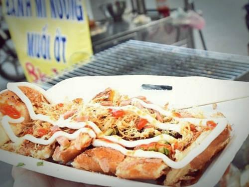 """Bánh mì nướng muối ớt: Đây là món ăn của người Khmer ở khu vực Bảy Núi (An Giang), lan dần ở các tỉnh miền Tây và đã tạo """"cơn sốt"""" ở TP. HCM thời gian qua. Bánh mì được quết muối ớt bên ngoài và nướng giòn trên bếp than. Sau đó cho thêm những gia vị hấp dẫn như phô mai, chà bông, ruốc tép, mỡ hành, xúc xích, pa-tê lên bề mặt thay vì bỏ vào trong ruột như bánh mì truyền thống… Một phần bánh mì nướng muốt ớt đầy đủ có giá 10.000 đồng, được bán nhiều ở đường Lê Quang Sung (quận 6), Tô Hiến Thành (quận 10) , Lam Sơn, Minh Phụng, Hàn Hải Nguyên (quận 11) . Ảnh: Má Lúm."""