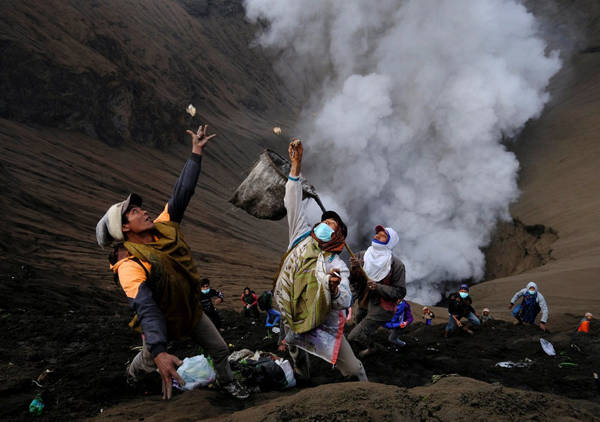 Nhiều người không sợ nguy hiểm, quay mặt về miệng núi lửa Bromo để bắt, chụp lấy lễ vật mà những tín đồ khác đã ném xuống.