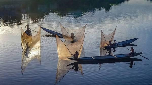 Khoảnh khắc các ngư dân đồng loạt thảlưới trên sông Hương ở Huế là thành quả của nhiếp ảnh Teberik Kolgeli.