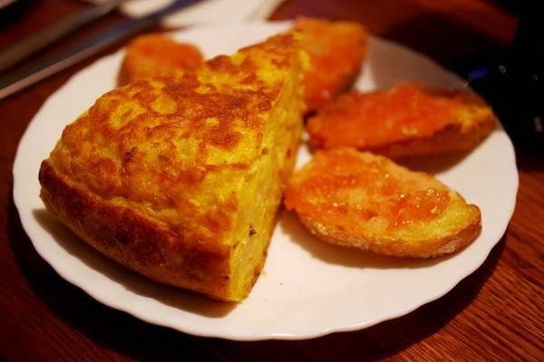 Omlette kiểu Tây Ban Nha được gọi là Tortilla Española, dùng khoai tây và trứng là nguyên liệu chính. Món này thường ăn kèm với những lát bánh mì nướng giòn đã phết sốt cà chua thơm ngon. Ảnh: Hương Chi.