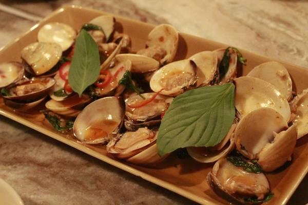 Nghêu xào với rau quế và sa tế Thái cay cay. Nói là món xào nhưng lại giống món nướng hơn nhờ cách chế biến khéo léo của đầu bếp. Vị nghêu được giữ nguyên vẹn, thịt béo, đậm đà, thơm mùi biển.